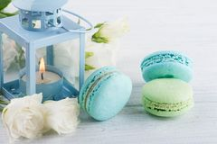 Arrangement of blue lanter, flowers, macaroons Royalty Free Stock Images