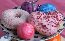 Colorful sweet doughnuts and easter eggs on a plate royalty free stock image