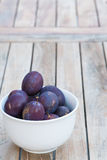 Arrangement of damson plums on wooden boards Stock Photos