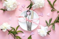 Arrangement de fête de table avec des couverts, des pivoines blanches et des coeurs sur la table rose Image libre de droits