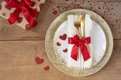 Arrangement de fête de table pour la Saint-Valentin avec la fourchette, le couteau, l'arc rouge, les cadeaux et les coeurs sur un image stock