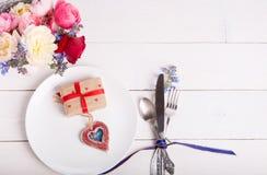 Arrangement de fête de table pour le jour du ` s de Valentine avec la fourchette, le couteau et les coeurs sur une table en bois  Photo stock
