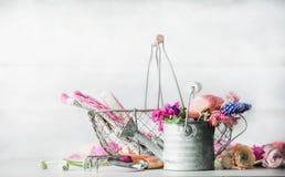Arrangement de jardinage avec la boîte d'arrosage, le panier, les outils de jardinage et les fleurs Photo stock