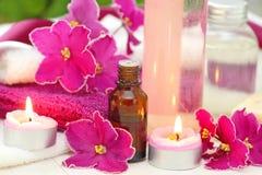 Arrangement de STATION THERMALE avec les bougies, l'huile d'arome et les violettes Photos stock