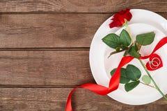 Arrangement de table de dîner de jour du ` s de Valentine avec le ruban rouge, rose et anneau au-dessus de fond de chêne Images libres de droits