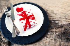 Arrangement de table de jour de valentines avec le plat blanc, fourchette, couteau, rouge Photo stock