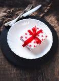 Arrangement de table de jour de valentines avec le plat blanc, fourchette, couteau, rouge Photographie stock libre de droits