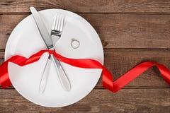 Arrangement de table de jour de valentines avec le plat, la fourchette, le couteau, l'anneau et le ruban Fond Photos stock