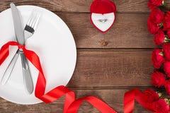 Arrangement de table de jour de valentines avec le plat, la fourchette, le couteau, l'anneau, le ruban et les roses Fond Photographie stock libre de droits
