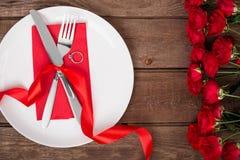 Arrangement de table de jour de valentines avec le plat, la fourchette, le couteau, l'anneau, le ruban et les roses Fond Images libres de droits
