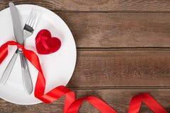Arrangement de table de jour de valentines avec le plat, la fourchette, le couteau, le coeur rouge et le ruban Fond Image stock