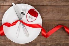 Arrangement de table de jour de valentines avec le plat, la fourchette, le couteau, le coeur rouge, l'anneau et le ruban Fond Photographie stock