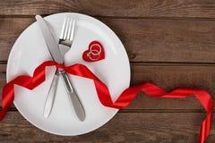 Arrangement de table de jour de valentines avec le plat, la fourchette, le couteau, le coeur rouge, l'anneau et le ruban Fond Images stock