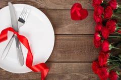 Arrangement de table de jour de valentines avec le plat, la fourchette, le couteau, le coeur rouge, le ruban et les roses Fond Images stock