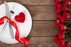 Arrangement de table de jour de valentines avec le plat, la fourchette, le couteau, le coeur rouge, le ruban et les roses Fond Photos stock