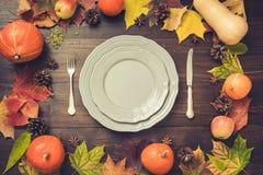 Arrangement de table de jour d'automne et de thanksgiving avec les feuilles tombées, les potirons, les épices, le plat gris et le images stock