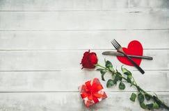 Arrangement de table de jour du ` s de Valentine avec la fourchette, le couteau, les coeurs rouges, le ruban et les roses Photographie stock