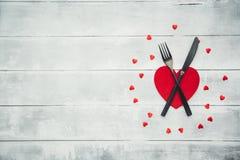 Arrangement de table de jour de valentines avec la fourchette, le couteau et la serviette de dîner rouge photographie stock