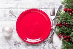 Arrangement de table de Noël avec le plat, le boîte-cadeau et l'argenterie rouges vides sur le fond en bois clair Branche d'arbre photographie stock libre de droits