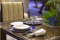 Arrangement de Tableau dans la couleur bleue dans le restaurant, plats, beaux verres, fleurs photos stock