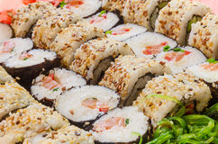 Arrangement of different sushi with a side of seaweed salad. Closely packed sushi rolls with some seaweed salad Stock Photo