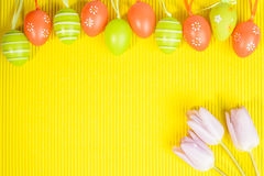 Arrangement of easter coloured eggs and tulips on yellow backgro Stock Images