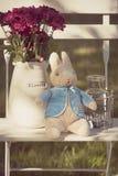 Arrangement estival de lapin et de bougie de fleurs sur une chaise blanche de style campagnard image libre de droits
