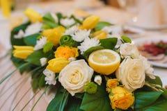 Arrangement floral avec des fleurs et la moitié d'un citron Images libres de droits