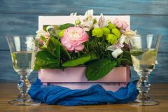 Arrangement with flowers. In a pink wooden box and wine Stock Photo