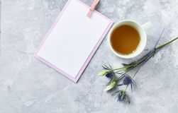 An arrangement of flowers, cup of tea and blank paper cards on gray background. Copy space Royalty Free Stock Photo