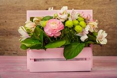 Arrangement with flowers. In a pink wooden box Stock Images