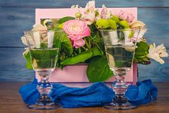 Arrangement with flowers. In a pink wooden box and wine Royalty Free Stock Image