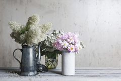 Arrangement of flowers standing on old wooden boards in dishes stock image