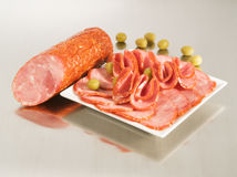 Arrangement with fresh Dry Crakow Sausage. Arrangement with fresh Dry Krakow Sausage on a steel silver board with olives royalty free stock photos