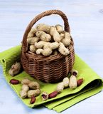 Peanuts with Nutshell. Arrangement of Fresh Peanuts with Nutshell in Wicker Basket on Green Napkin closeup on Wooden background Royalty Free Stock Images