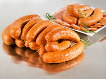 Arrangement with fresh pork sausage. On a steel silver board Stock Photos