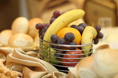 Arrangement of fruits. On a celebration table: banana, apple, grapes Royalty Free Stock Photos