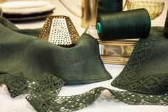 Arrangement of green vintage lace, green linen, a spool of green thread and brass accessories. Vintage and needlework royalty free stock image