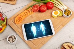 Arrangement of healthy Ingredients with a tablet. royalty free stock photo