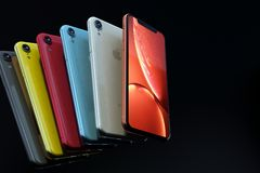 Arrangement of iPhone XR all colours, horizontal. Multiple smartphones - iPhone XR Silver, Space Grey, Red, Blue, Yellow and Coral, arranged in a row formation royalty free stock photo