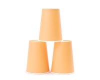 Arrangement of orange recycling paper glasses on white backgroun. Row of recycling paper glass Royalty Free Stock Photo