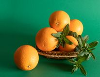 Arrangement of oranges in a bowl decorated with mint in natural light stock images