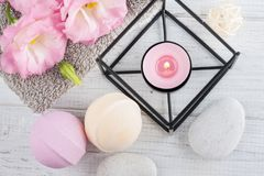 SPA composition with bath bombs. Arrangement of pink eustoma flowers, towels, lit candle. SPA composition with bath bombs Stock Images
