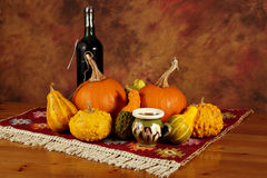 Arrangement of pumpkins, squashes and bottle of wine Stock Photography