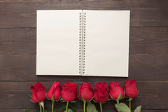 The arrangement of red roses flower with notebook are on the woo Stock Photo