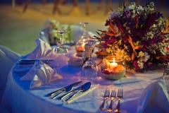 Arrangement romantique de dîner sur la plage au coucher du soleil Photo stock