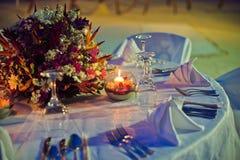 Arrangement romantique de dîner sur la plage au coucher du soleil Photos stock