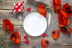 Arrangement romantique de table avec des couverts et des pavots rouges sur l'OE rustique Image stock