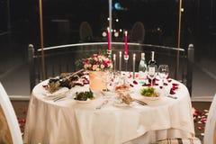 Arrangement romantique de table avec du vin, de belles fleurs dans la boîte, verres vides, pétales de rose et bougies photo libre de droits