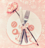 Arrangement romantique de table avec le plat, la fleur rose, les couverts et le ruban sur le fond de rose en pastel Photo stock